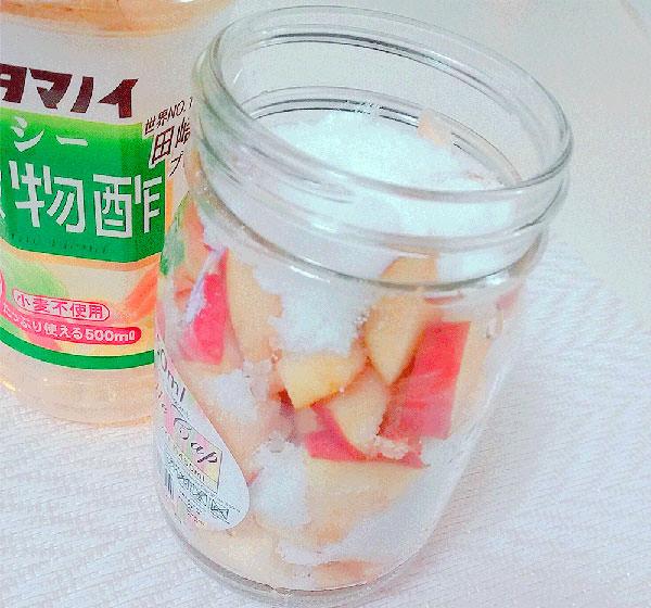 リンゴが入っている容器に砂糖を入れる