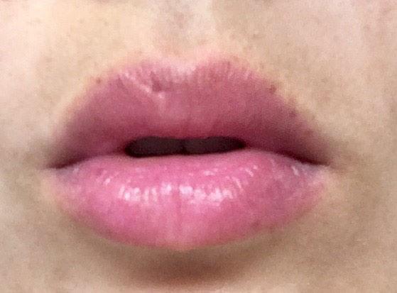 唇にジューシーレディリキッドチーク「01 ローズポップ」を塗る