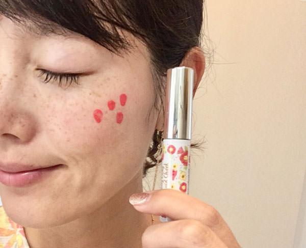 キャンメイク ジューシーレディリキッドチーク「03 アップルチェリー」を頬に塗る